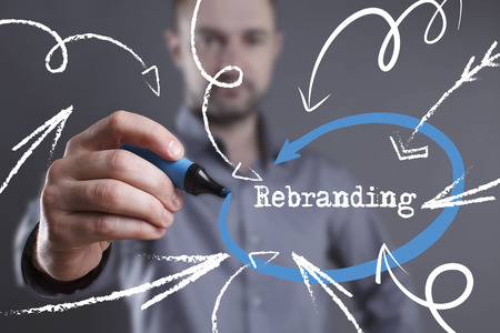 Technology, internet, business and marketing. Young business man writing word: Rebranding Stock Photo