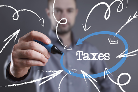 Technology, internet, business and marketing. Young business man writing word: Taxes