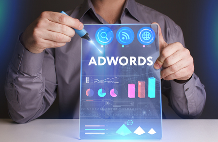 Business, Technology, Internet and network concept. Young businessman working on a virtual screen of the future and sees the inscription: AdWords Stock Photo