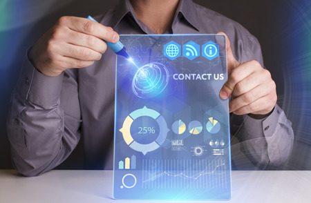 advertise with us: Business, Technology, Internet and network concept. Young businessman working on a virtual screen of the future and sees the inscription: Contact us Stock Photo