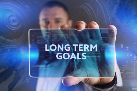 long term: Business, Technology, Internet and network concept. Young businessman working on a virtual screen of the future and sees the inscription: Long term goals