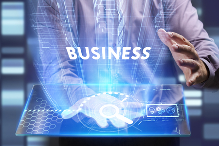 Business, Technology, Internet and network concept. Young businessman working on a virtual screen of the future and sees the inscription: Business Stock Photo