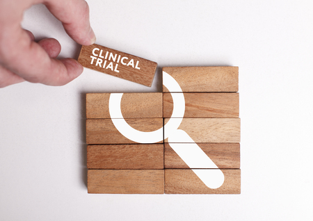 Business, Technology, Internet and network concept. Young businessman shows the word: Clinical trial
