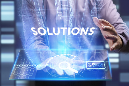 Business, Technology, Internet and network concept. Young businessman working on a virtual screen of the future and sees the inscription: Solutions Stock Photo