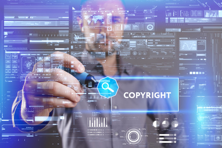keyword: Business, Technology, Internet and network concept. Young businessman working on a virtual screen of the future and sees the inscription: Copyright Stock Photo