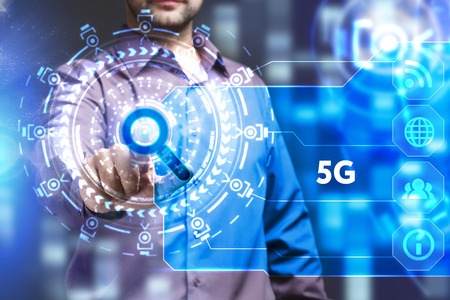 Business, Technology, Internet and network concept. Young businessman working on a virtual screen of the future and sees the inscription: 5G Stock Photo