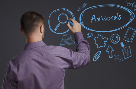 adwords: Business, Technology, Internet and network concept. A young businessman writes on the blackboard the word: AdWords