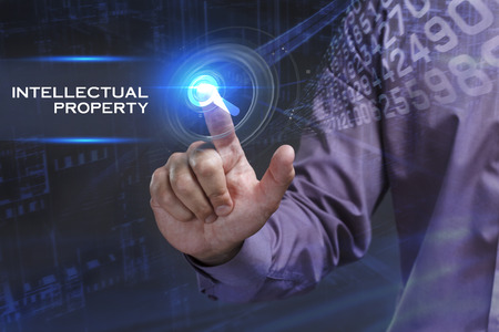 keyword: Business, Technology, Internet and network concept. Young businessman working on a virtual screen of the future and sees the inscription: Intellectual property