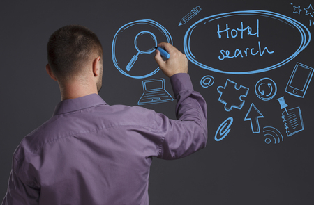 keyword: Business, Technology, Internet and network concept. A young businessman writes on the blackboard the word: Hotel search
