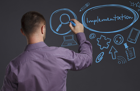 keyword: Business, Technology, Internet and network concept. A young businessman writes on the blackboard the word: Implementation Stock Photo