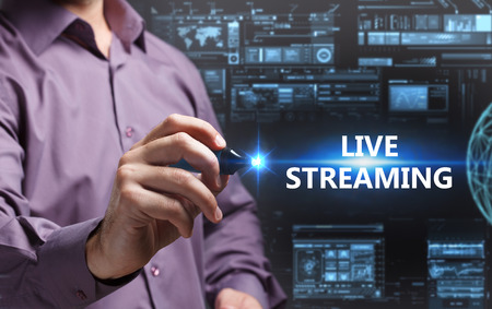 keyword: Business, Technology, Internet and network concept. Young businessman working on a virtual screen of the future and sees the inscription: Live streaming