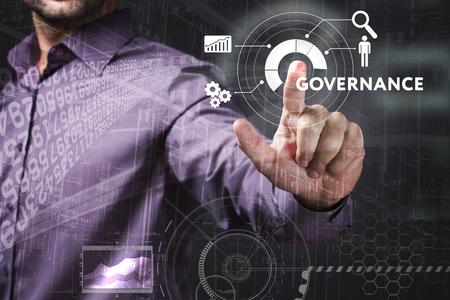 Affaires, Technologie, Internet et le concept de réseau. Jeune homme d'affaires travaillant sur un écran virtuel de l'avenir et voit l'inscription: Gouvernance