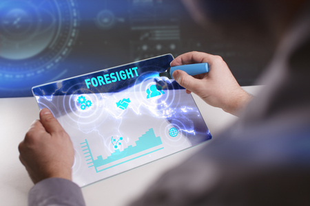 Business, Technology, Internet and network concept. Young businessman working on a virtual screen of the future and sees the inscription: Foresight Stock Photo