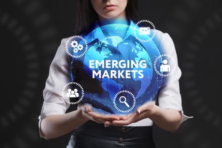 비즈니스, 기술, 인터넷 및 네트워크의 개념. 미래의 가상 스크린에서 일하는 젊은 사업가가 비문을 봅니다 : 신흥 시장