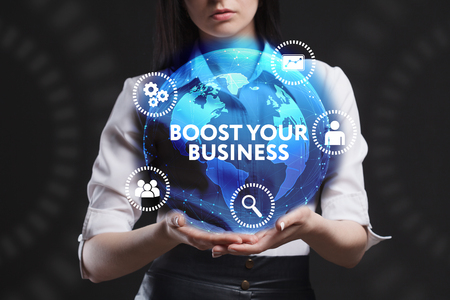 The concept of business, technology, the Internet and the network. A young entrepreneur working on a virtual screen of the future and sees the inscription: Boost your business