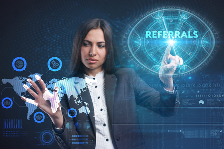 keywords: The concept of business, technology, the Internet and the network. A young entrepreneur working on a virtual screen of the future and sees the inscription: Referrals Stock Photo