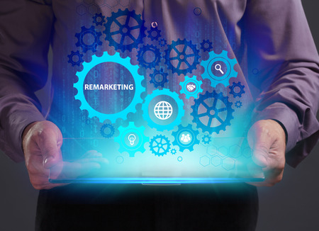 Business, Technology, Internet and network concept. Young businessman working on a virtual screen of the future and sees the inscription: Remarketing Stock Photo