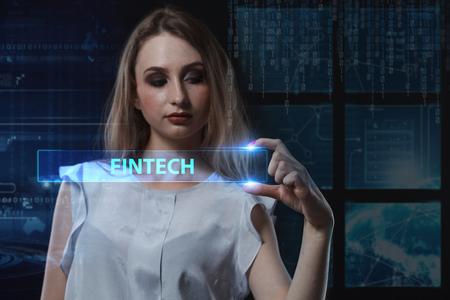 niche: The concept of business, technology, the Internet and the network. A young entrepreneur working on a virtual screen of the future and sees the inscription: Fintech