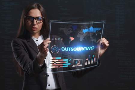 niche: The concept of business, technology, the Internet and the network. A young entrepreneur working on a virtual screen of the future and sees the inscription: Outsourcing