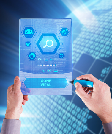 The concept of business, technology, the Internet and the network. A young entrepreneur working on a virtual screen of the future and sees the inscription: Gone viral Stock Photo