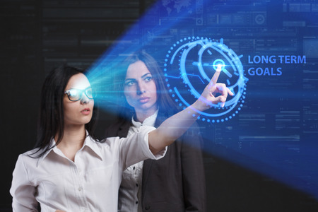 The concept of business, technology, the Internet and the network. A team of business women working on the virtual screen of the future and see the inscription: Long term goals Stock Photo