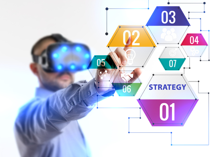 Business, Technology, Internet and network concept. Young businessman working in virtual reality glasses sees the inscription: Strategy Stock Photo