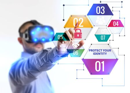 Business, Technology, Internet and network concept. Young businessman working in virtual reality glasses sees the inscription: Protect your identity