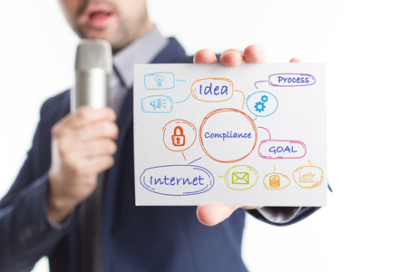 keywords: The concept of business, technology, the Internet and the network. Young businessman showing inscription: Compliance