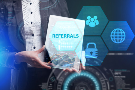 The concept of business, technology, the Internet and the network. A young entrepreneur working on a virtual screen of the future and sees the inscription: Referrals Lizenzfreie Bilder
