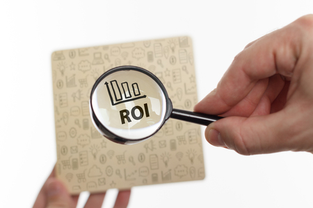 The concept of business, technology, the Internet and the network. Young businessman showing inscription: ROI Stock Photo