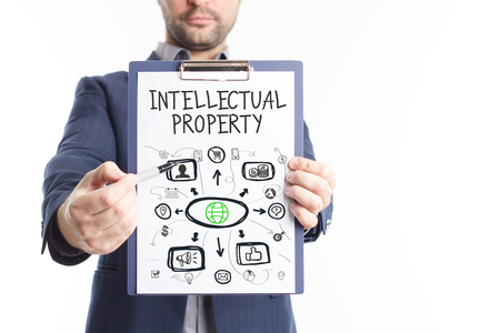 The concept of business, technology, the Internet and the network. A young businessman shows a successful scheme of work: Intellectual property