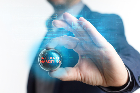 The concept of business, technology, the Internet and the network. A young entrepreneur working on a virtual screen of the future and sees the inscription: Influence marketing