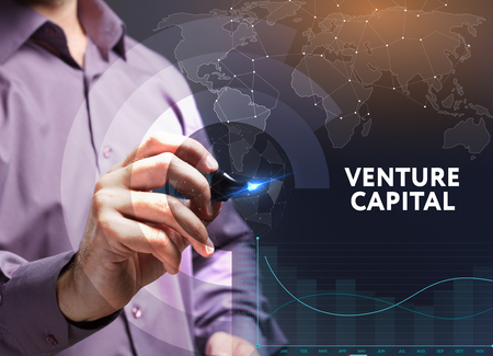 The concept of business, technology, the Internet and the network. A young entrepreneur working on a virtual screen of the future and sees the inscription: Venture capital