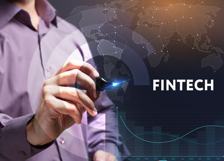 The concept of business, technology, the Internet and the network. A young entrepreneur working on a virtual screen of the future and sees the inscription: Fintech