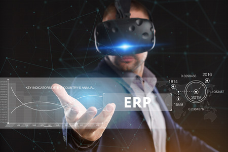 Business, Technology, Internet and network concept. Young businessman working in virtual reality glasses sees the inscription: ERP