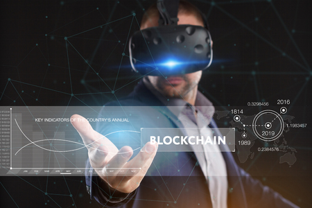 Business, Technology, Internet and network concept. Young businessman working in virtual reality glasses sees the inscription: blockchain