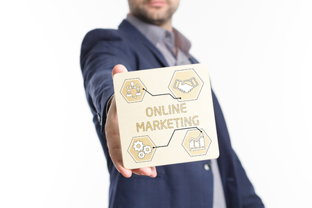 The concept of business, technology, the Internet and the network. Young businessman showing inscription: Online marketing