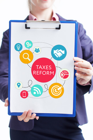 Business, technology, internet and networking concept. Young entrepreneur showing keyword: taxes reform Stock Photo - 119163097