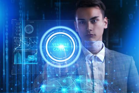 Het concept van business, technologie, internet en het netwerk. Een jonge ondernemer werkt aan een virtueel scherm van de toekomst en ziet het opschrift: Venture capital