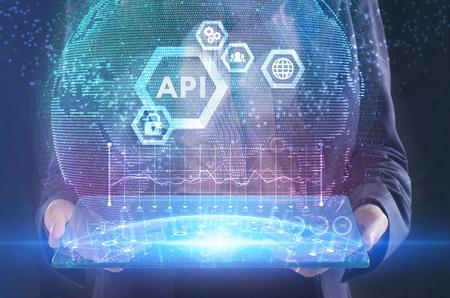 Het concept van business, technologie, internet en het netwerk. Een jonge ondernemer werkt aan een virtueel scherm van de toekomst en ziet het opschrift: API