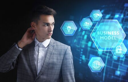 The concept of business, technology, the Internet and the network. A young entrepreneur working on a virtual screen of the future and sees the inscription: Business model Stock Photo