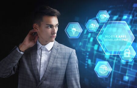 The concept of business, technology, the Internet and the network. A young entrepreneur working on a virtual screen of the future and sees the inscription: Mobile apps development Фото со стока