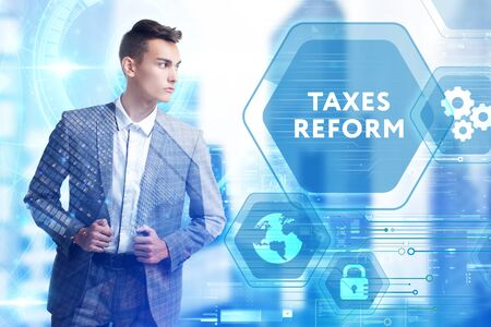 The concept of business, technology, the Internet and the network. A young entrepreneur working on a virtual screen of the future and sees the inscription: taxes reform