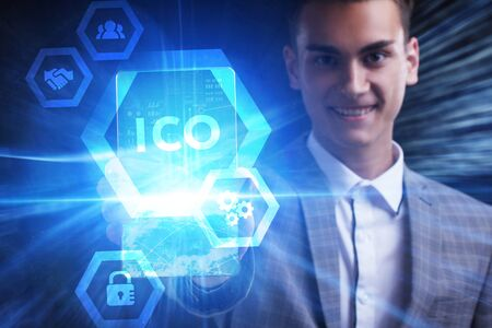 The concept of business, technology, the Internet and the network. A young entrepreneur working on a virtual screen of the future and sees the inscription: ICO