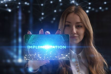 The concept of business, technology, the Internet and the network. A young entrepreneur working on a virtual screen of the future and sees the inscription: Implementation