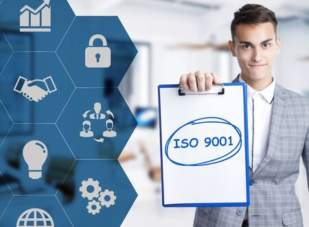 Business, technology, internet and network concept. Young businessman shows a keyword: ISO 9001