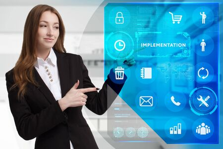 Business, Technology, Internet and network concept. Young businessman working on a virtual screen of the future and sees the inscription: Implementation Stock fotó - 133489577