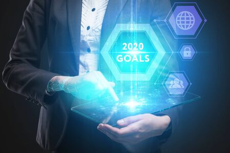 Business, Technology, Internet and network concept. Young businessman working on a virtual screen of the future and sees the inscription: 2020 goals