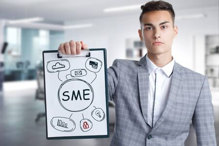 Business, Technology, Internet and network concept. Young businessman working on a virtual screen of the future and sees the inscription: SME