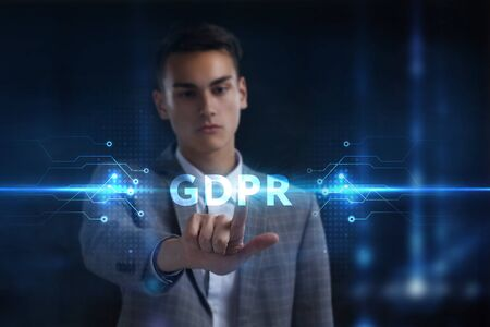 Business, Technology, Internet and network concept. Young businessman working on a virtual screen of the future and sees the inscription: GDPR Фото со стока